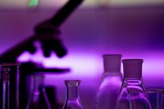 Empty chemical glassware on color background. Group of laboratory empty flasks on color scientific background reflection on a stock photo