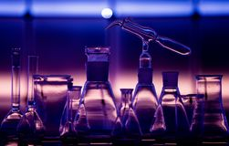 Empty chemical glassware on color background. Group of laboratory empty flasks on color scientific background reflection on a royalty free stock photography