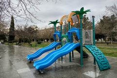 An empty children playground in city park at rainy weather. An empty children playground in city park at rainy cloudy weather Royalty Free Stock Images