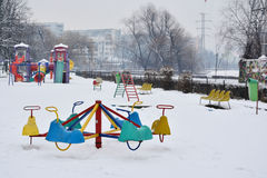 Empty children playground in the snow. Stock Photos