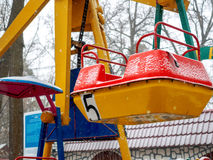 Empty children`s colourful attractions in the park during snowfall. In the fall Royalty Free Stock Images