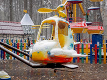 Empty children`s colourful attractions in the park during snowfall. In the fall Royalty Free Stock Image