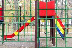 Empty children's playground and a slide in the park. Against the backdrop of autumn trees with fallen leaves. Selective focus with a blurred background Royalty Free Stock Photos