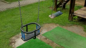 Empty children`s swings on a chain swinging. On the playground with grass stock video