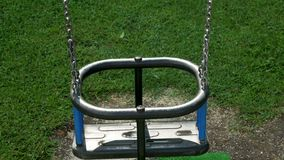 Empty children`s swings on a chain swinging. On the playground with grass stock footage