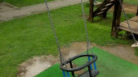 Empty children`s swings on a chain swinging. On the playground with grass stock video footage