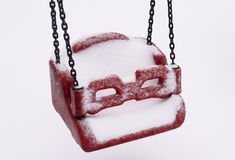 Empty children swing covered in snow Royalty Free Stock Photography