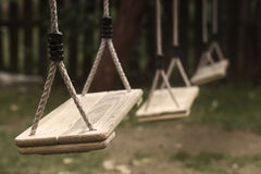 Empty children swings in the park. Horizontal perspective view of three wooden child swings in the park with shallow depth of field Stock Photography