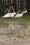 Empty children swings in the park. Vertical perspective view of three wooden child swings in the park with shallow depth of field Royalty Free Stock Images