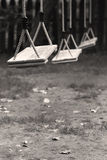 Empty children swings in the park. Vertical perspective view of three wooden child swings in the park with shallow depth of field Royalty Free Stock Photography