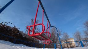 Empty children swings on a playground in city park at sunny winter day, view from the bottom, backlight, wide angle. 4k stock footage