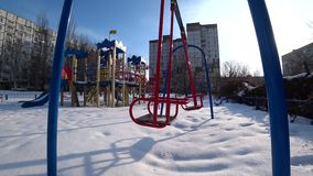 Empty children swings on a playground in city park at sunny winter day, view from the bottom, backlight, wide angle. 4k stock video