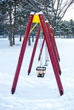 Empty children swings in a winter park Royalty Free Stock Photo