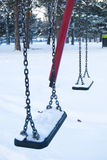 Empty children swings in a winter park Stock Photo