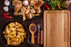 Empty chopping board, grilled chicken wings, baked potatoes in a stock image