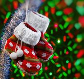 Empty christmas boots and fluffy garland on dark background with blurred lights. Blurred vignette Royalty Free Stock Image