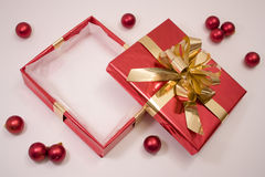 Empty Christmas Box. Empty box christmas present with some red bauble around Royalty Free Stock Image