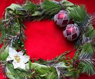 Empty christmas frame. On red background with poinsettia holly and red ornaments royalty free stock photo