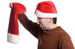 Empty Christmas Stocking. Profile view of a man wearing a Santa hat looking disgusted that his stocking is empty, isolated against a white background Stock Image