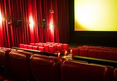 Empty cinema with blank screen and rows of red seats. Large curtains on side stock image