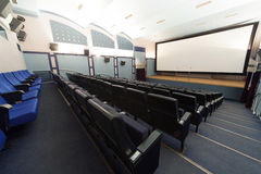 Empty cinema hall, view from the back door. Royalty Free Stock Photos