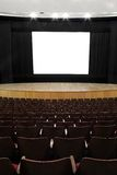 Empty cinema screen. Cinema, wooden seats and stage, black screen mask, white empty screen (1:1,37 Stock Photo