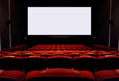 Empty cinema seats with blank white screen Stock Image