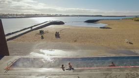 Empty city beach of Reykjavik in good sunny weather, people are sitting in pool with warm water. 4K stock video