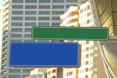Empty city signs. One green and one blue empty street signs, buildings in background Stock Photography