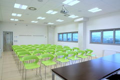 Empty classroom. With windows on the right and empty green chair Stock Image