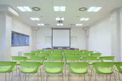 Empty classroom. With green chair and a board in the backgruond and a window on the left Stock Photo