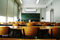 Empty Classroom. A large, empty classroom with wooden chairs