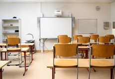 Empty classroom with an interactive whiteboard, desks and chairs. Selected focus stock photography