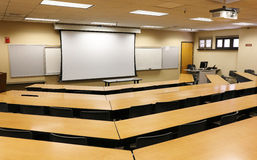 Empty Classroom with Projector & Blank Screen. An empty classroom with projector screen and whiteboard Stock Photo
