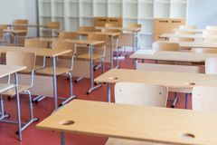 Empty classroom with wooden desks and chairs. School interior stock photo