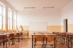 Empty classroom with wooden desks. Empty classroom interior with wooden desks, large bright windows and white board royalty free stock image