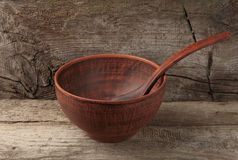 Empty clay bowl with spoon on wooden background Stock Photography