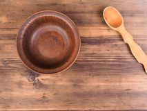 Empty clay bowl with wood spoon on old wooden table. Rural composition, top view. Template for menu, poster or print royalty free stock photos