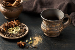 Empty clay cup with natural aroma spices blend, cardamon, anise, cinnamon, in rustic ceramic on dark table Royalty Free Stock Photography