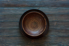 Empty clay plate over wood background. Royalty Free Stock Photo