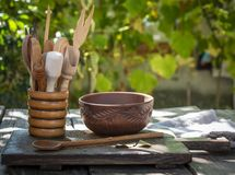Empty clay plate and various wooden kitchen objects Stock Image