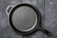Empty, clean black cast iron pan or dutch oven top view from above on black table. Empty, clean black cast iron pan or dutch oven top view from above on black stock images