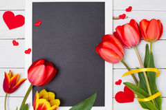 Empty clean black chalkboard with red tulips and hearts. Top view. Royalty Free Stock Photos