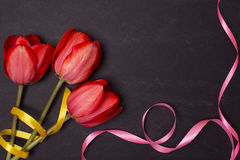Empty clean black chalkboard with red tulips and ribbons. Top view. Stock Photos