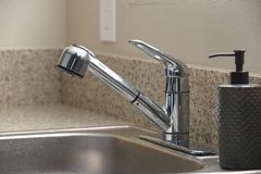 Empty clean kitchen sink and soap dispenser. Empty clean stainless steel kitchen sink and soap dispenser Royalty Free Stock Photography