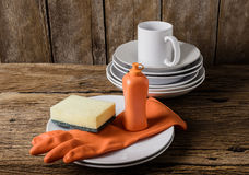 Empty clean plates and cup with dishwashing liquid, sponges, rub Royalty Free Stock Photos