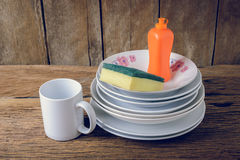 Empty clean plates and cup with dishwashing liquid, sponges Royalty Free Stock Photography