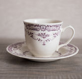 Empty clear vintage coffee cup with purple floral pattern Stock Photography