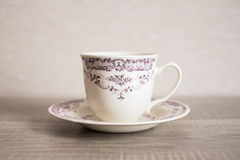 Empty clear vintage coffee cup with purple floral pattern Stock Photo