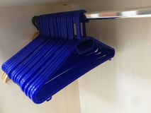 Empty clothes hangers in the closet. Blu stock photos